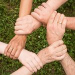 six people holding each other's wrists