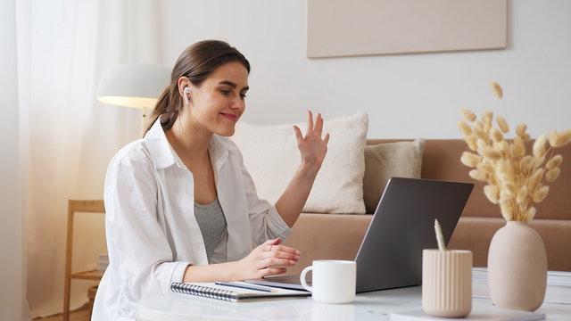woman waving to computer