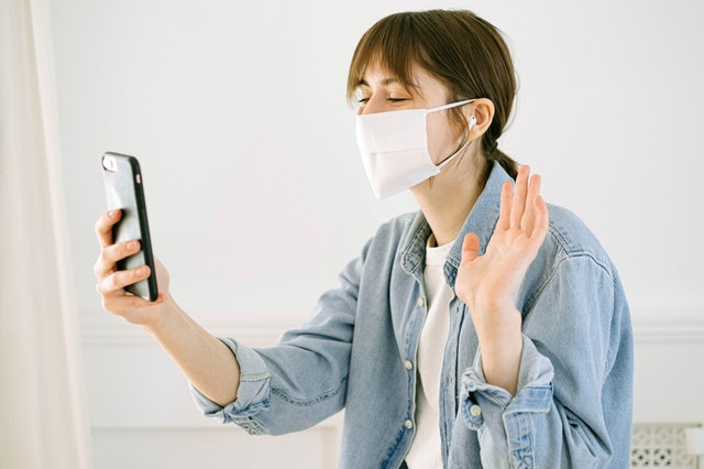 Woman in mask waving to phone